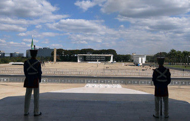 Soldiers of the presidential guard with the Supreme Court building in the background stand at Planalto Palace in Brasilia