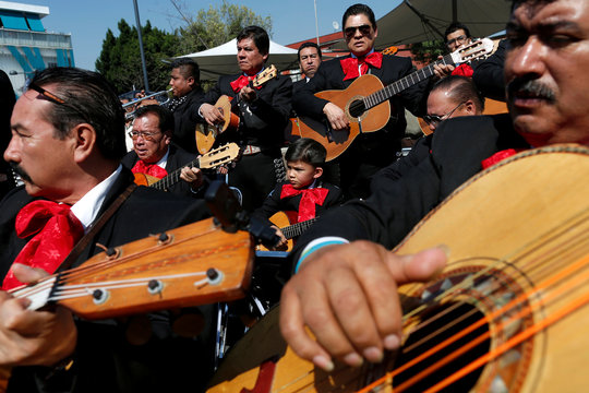 A child plays the guitar with a Mariachi band during a service to celebrate Santa Cecilia, patron of musicians in Mexico City, Mexico