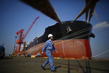 A worker walks next to a vessel which is under construction at the Waigaoqiao shipyard in Shanghai