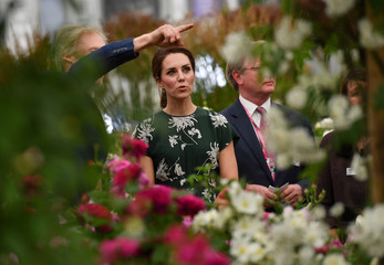 Britain's Catherine, Duchess of Cambridge reacts as she views a display of David Austin roses at the Chelsea Flower Show in London