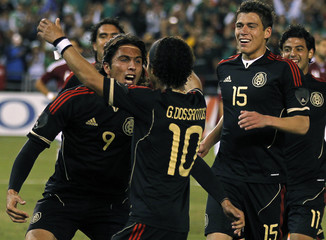 Mexico's Aldo DeNigris celebrates with teammates Giovani Dos Santos and Hector Moreno after scoring against Venezuela during the second half of their international friendly soccer match in San Diego