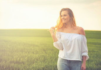 Happy smiling woman in green field at sunny day
