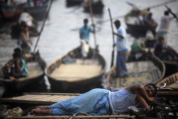 A man sleeps on a rickshaw van as boats wait to dock by the river Buriganga in Dhaka
