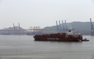 Hamburg Sud ship carrying containers arrives as Hyundai Merchant Marine container terminal is seen in background at Busan New Port