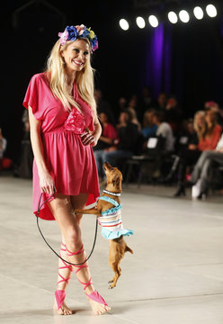 """Model Jimena Cyrulnik walks with a dog presenting a creation by designers Reichardt and Schiavo during the so-called """"2013 Spring-Summer Caribbean Colour Paws"""" show in Buenos Aires"""