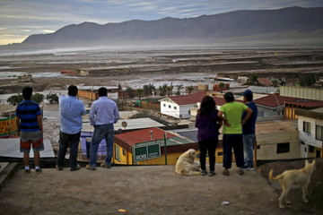 Locals gather in front of a flooded area at Chanaral town