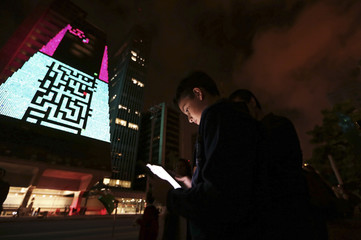 """A boy uses an iPad to play a game, which is projected onto the Fiesp building, during the """"Play!"""" exhibition in Avenida Paulista"""