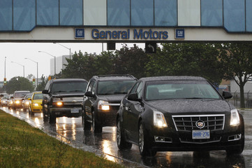 A line up of cars is seen on a road after a shift change at the General Motors Car assembly plant in Oshawa