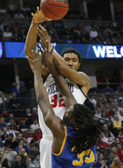 Richmond forward Justin Harper passes over Morehead State center Kenneth Faried during the first half of their third round NCAA tournament basketball game in Denver