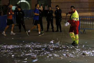 A worker covering essential services cleans paper and trash strewn on the pavement outside Madrid's Town Hall after a demonstration against layoffs and salary cuts during an indefinite strike by street cleaners in Madrid