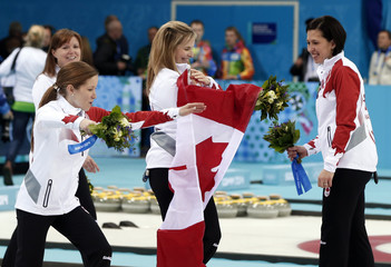 Canada's vice Lawes, alternate Gray, skip Jones and second Officer celebrate with their bouquets during flower ceremony for women's curling during Sochi 2014 Winter Olympics
