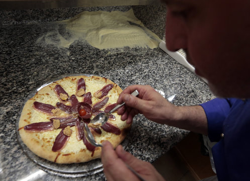 Maurizio Scalia, an Italian chef and teacher at the French pizzaiolo school, prepares a pizza with filet of duck breast and foie gras in Cap D'Ail