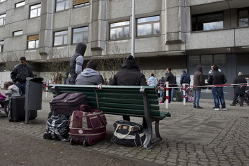 Asylum seekers stand outside the central receiving facility for refugees in Berlin
