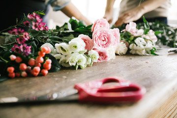 цветы лежат на столе, где девушки флористы работают над созданием букета he flowers are on the table, where the girls florists design a bouquet