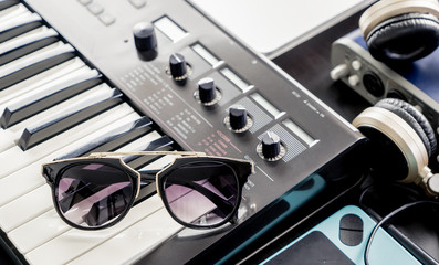 Fashionable Sunglasses on Music keyboard in studio