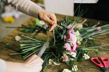 Девушка флорист собирает красивый букет girl florist makes a...