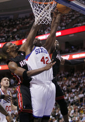 Philadelphia 76ers forward Brand shoots between defense of Miami Heat forward Bosh and Miami guard Wade in Philadelphia