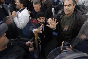Protesters chant slogans in front of a policeman during a demonstration in Algiers