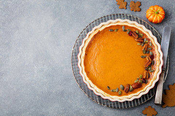 Tasty pumpkin pie, tart made for Thanksgiving day in a baking dish. Grey stone background. Top view