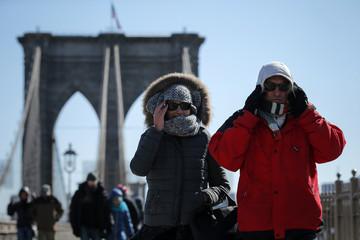 People walk during low temperatures through the Brooklyn bridge in New York