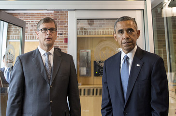 U.S. President Obama speaks as Deputy Chief of Mission Mollema listens, after signing the book of condolence for the Malaysia Airlines Flight MH17 disaster, at the Embassy of the Netherlands in Washington