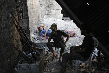 Free Syrian Army fighters talk with each other as another rests in Aleppo's Qastal al-Mosht district