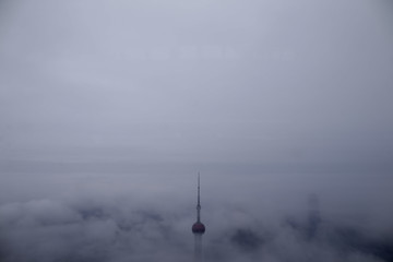 The Oriental Pearl Tower skyscraper is seen from the Shanghai World Financial Center during rain at the financial district of Pudong in Shanghai