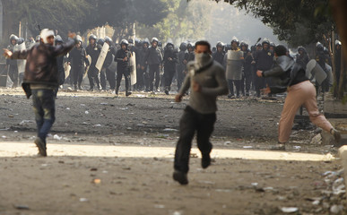 Protesters run during clashes with security forces near the Interior Ministry in Cairo