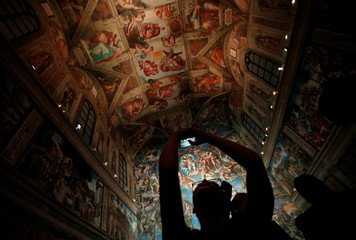 A visitor takes a picture with her cellphone at a full-size replica of the Sistine Chapel after the opening ceremony in Mexico City