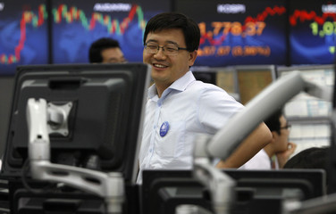 A foreign currency dealer of the Korea Exchange Bank smiles as he works in front of a screen displaying the KOSPI at the bank's dealing room in Seoul