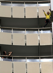 Hotel guests take pictures of French urban climber Alain Robert, also known as Spiderman, celebrating as he reached the top floor of a hotel in Bucharest