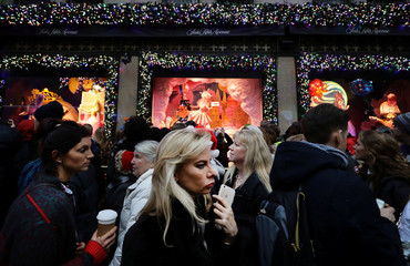 People crowd down Fifth Avenue during a busy shopping day in Manhattan