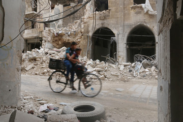 Boys ride a bicycle past damaged buildings on a street in the old city of Aleppo