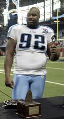 File photo shows Titans' Haynesworth holding a spoon as he gets ready to eat fruit cobbler after a Thanksgiving Day NFL football game in Detroit