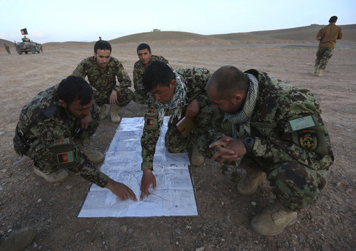 Afghan National Army soldiers look at a military map outside a military base in the Adraskan district of Herat province
