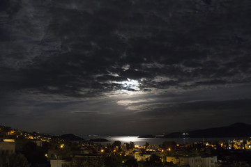 Long exposure of full moon in 2016 summer behind clouds over Aegean sea at Turkbuku village in Bodrum peninsula. Light shines on sea surface.