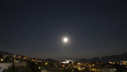 Long exposure of full moon in 2016 summer over Aegean sea at Turkbuku village in Bodrum peninsula. Light shines on sea surface.