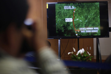 A photographer takes a picture of a screen showing a map of Iguala during a news conference by Mexico's Attorney General Jesus Murillo Karam in Mexico City