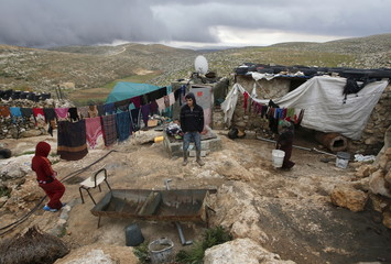 Palestinians stand outside their shed during snow storm, south of Hebron