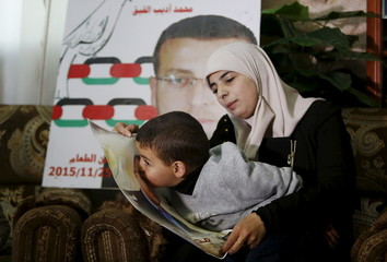 The wife of Palestinian journalist Mohammed al-Qeq holds her son as he kisses his father's picture during a TV interview with Reuters, south of Hebron