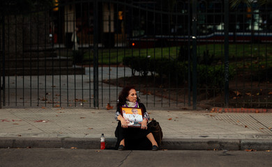 A woman sits on the kerb holding an image of Pope Francis as she waits for the Via Crucis (Way of the Cross) procession in Buenos Aires