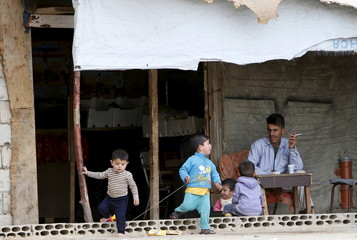 Children play beside a man resting inside a compound for Syrian Refugees in Sidon, south Lebanon
