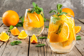 Summer refreshing orange drink. Detox, diet, infused. Variations on lemonade. Mineral water with pieces of fresh orange and mint. On a rustic wooden table with grey wall. Vertical, copy space