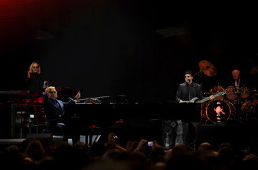 British singer-songwriter Elton John performs with his band during a concert in Gijon