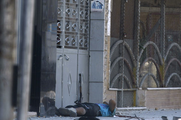 A Free Syrian Army fighter lies on the ground after he was shot by a sniper at Seif a Dawla district in Syria's northwestern city of Aleppo
