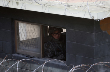 A South Korean soldier watches at a checkpoint near the demilitarized zone separating North Korea from South Korea, in Paju