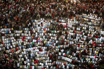 People pray as thousands gather in Tahrir Square to listen to a speech by newly elected president Mohamed Mursi at Cairo's Tahrir square