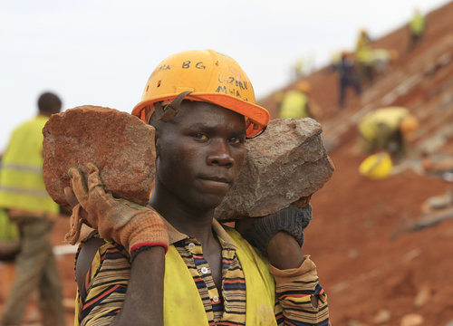 Construction worker carries stones as he works at a landscaping section of the Mombasa-Nairobi standard gauge railway near Emali