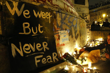 REPEATING CORRECTING BYLINE - Flowers and candles are placed near the scene of a shooting the day after a series of deadly attacks in Paris