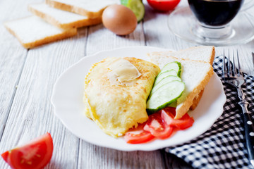 Hearty and tasty breakfast, traditional in the hotel, omelette from chicken eggs with cheese, fresh vegetables - cucumber and tomato, white toast and black coffee on a light wooden background